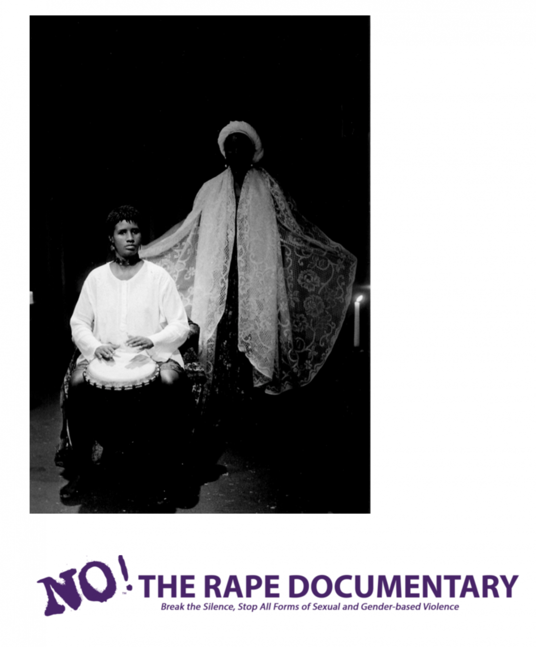 A black and white, still image from the film showing a Black person in a white tunic sitting and playing a drum with their hands, and another person in a lacy white cape standing behind them with their arms partially outstretched.