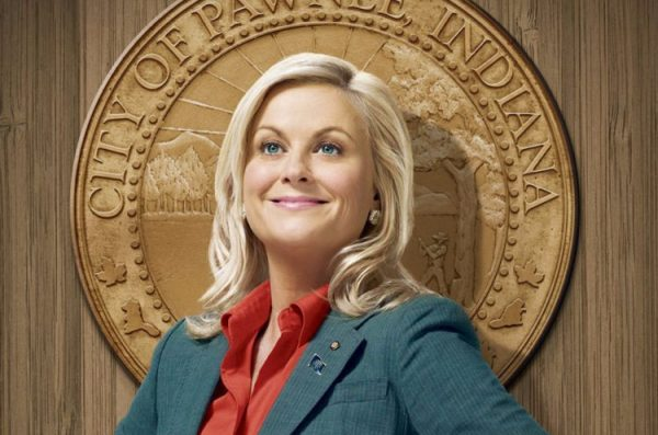 Leslie Knope from the TV show Parks and Recreation stands proudly before the town seal