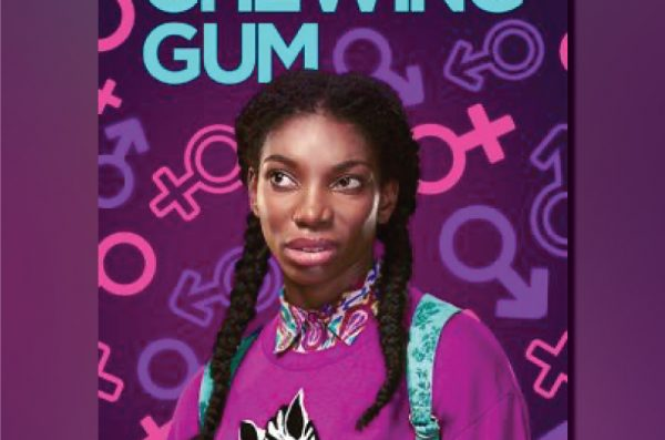 A young Black woman with two braids, wearing a pink sweater with a zebra on the front, makes an awkward face toward something off-camera.