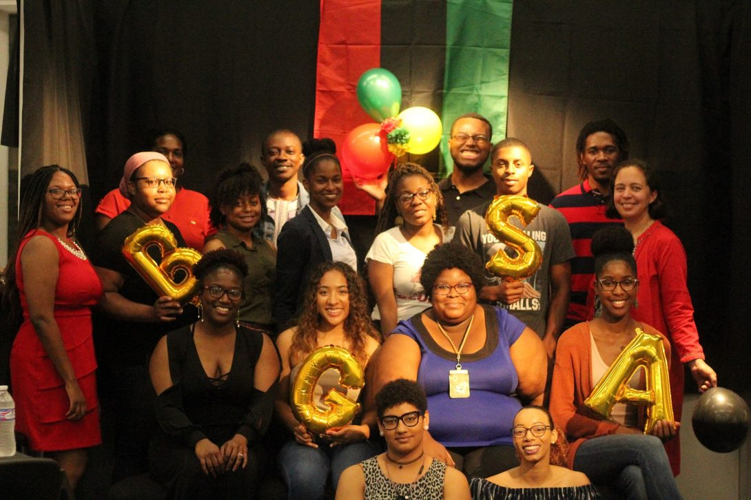 A group of Black Graduate Student Association members holds balloons of the letters