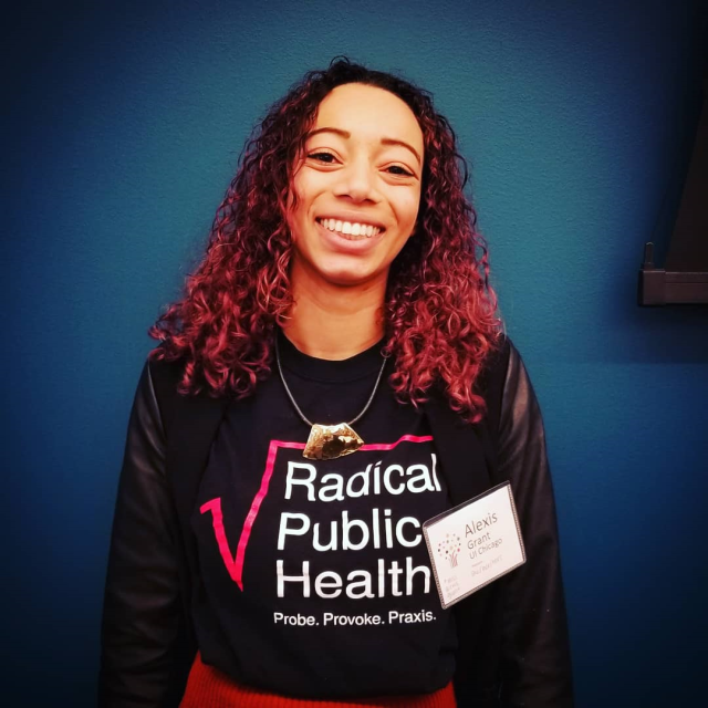 Alexis Grant, wearing a Radical Pubic Health shirt, smiling toward the camera