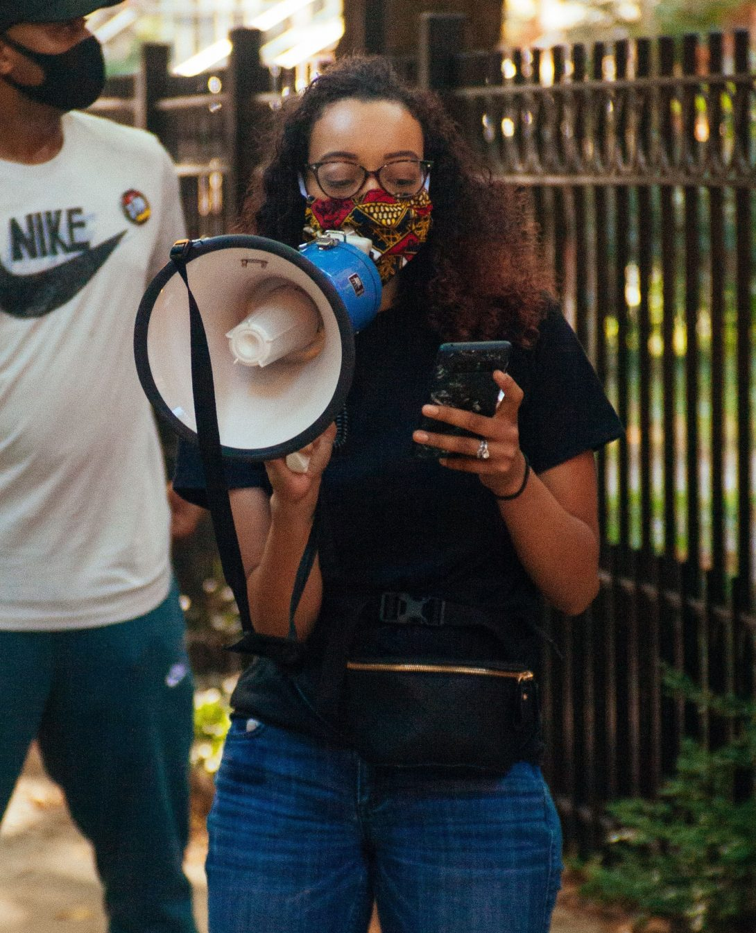 Alexis, wearing a face mask, standing outdoors near a fence, reading off a phone, and speaking through a megaphone.