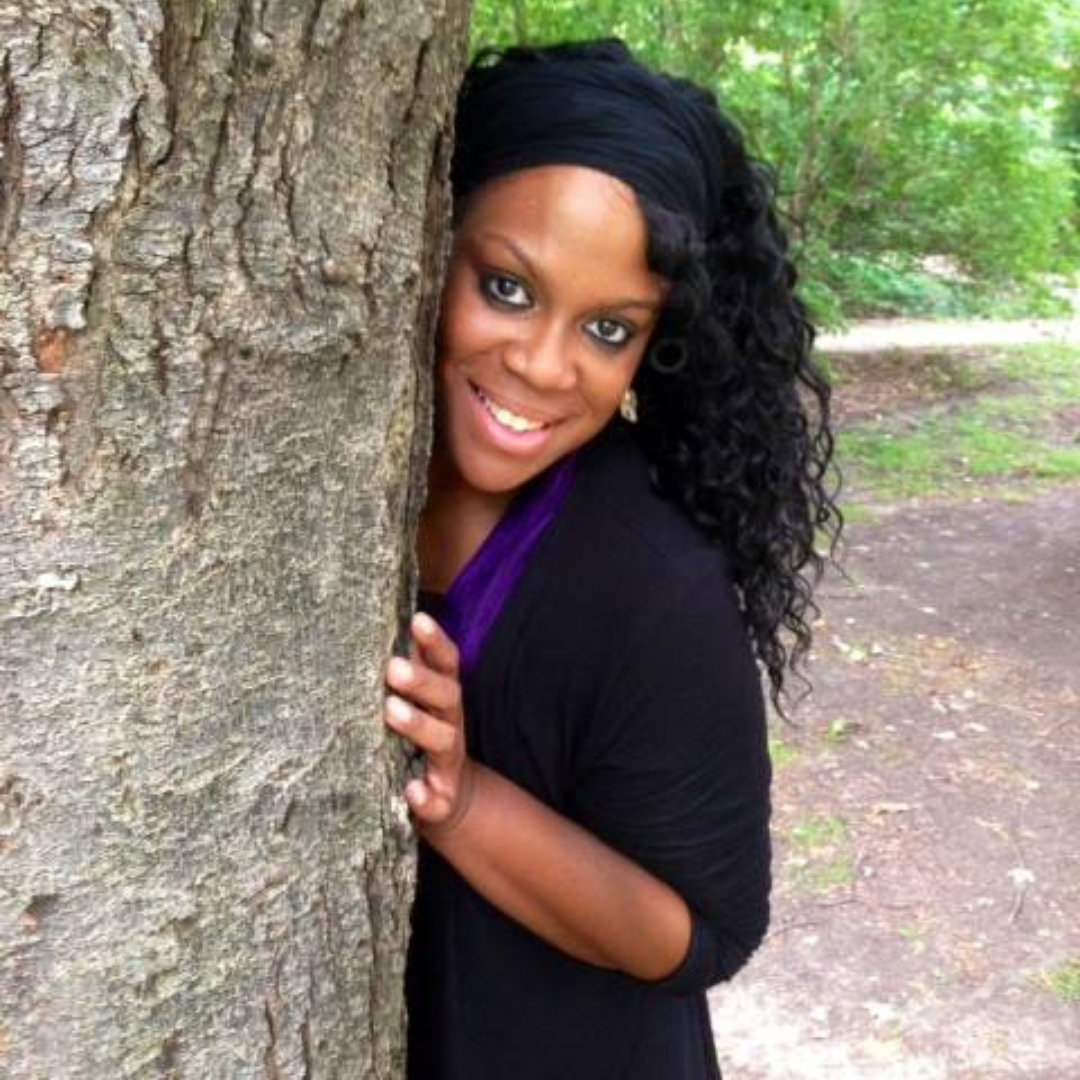 Crystal Schwartz, wearing a purple top and a black sweater, peeks out from behind a big tree.