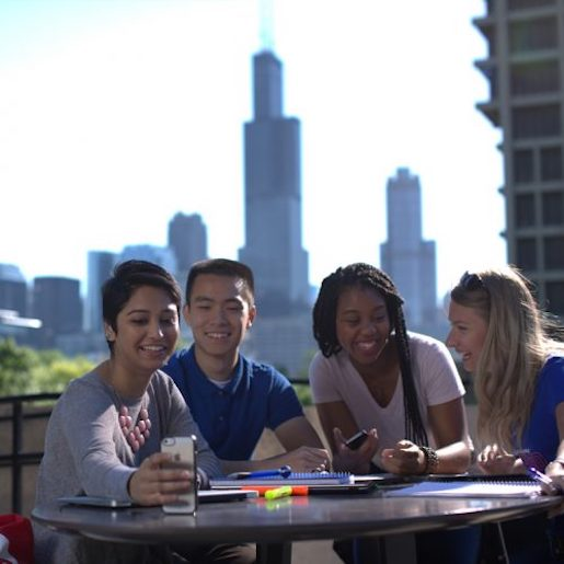 Four smiling students sit at a round table outside. Two are posing for a selfie. The Willis/Sears Tower and UIC's University Hall can be seen in the background.