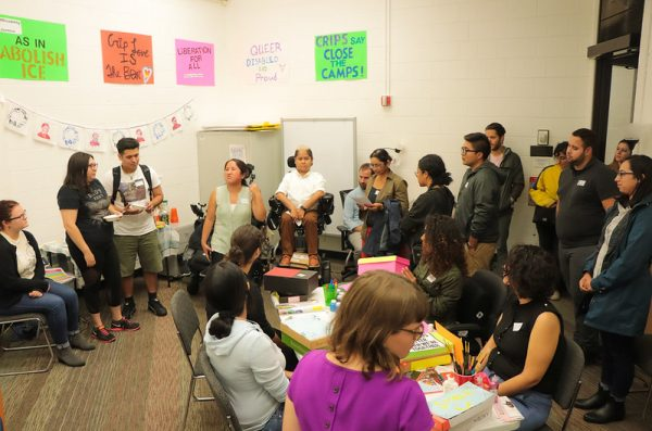 A wide shot of the DCC lounge shows guests standing and sitting in various locations in the room while listening to DCC Program Coordinator, Lily Diego-Johnson speak.