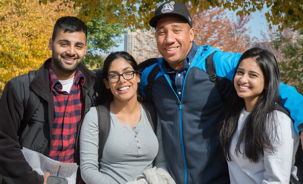 4 students standing together and smiling toward the camera
